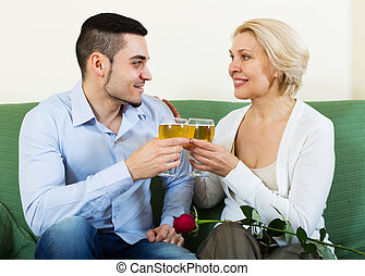 Handsome guy and elderly woman drinking wine