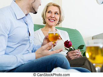 guy and elderly woman drinking wine