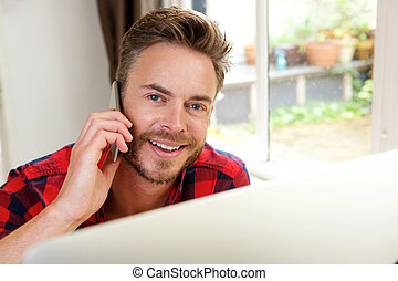 Handsome guy at home office on phone