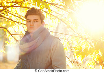 Handsome guy backlighting portrait with bokeh, outdoor in autumn park.