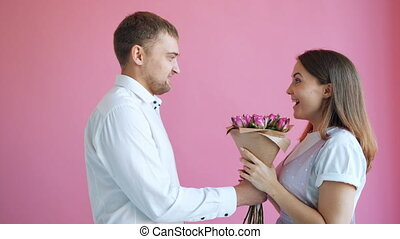 Handsome guy is bringing bunch of flowers to beloved woman kissing smiling feeling and expressing love on pink background. Relationship, dating and valentine's day.