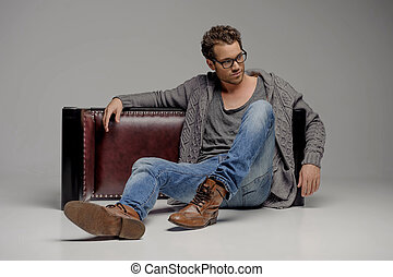 Handsome guy. Handsome young men in glasses sitting on the floor and looking away while isolated on grey
