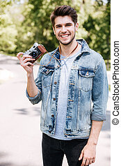 Handsome guy holding camera outdoors