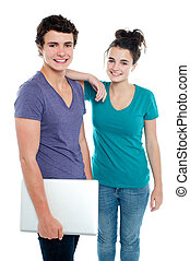 Handsome guy holding laptop posing with his girlfriend