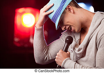 handsome guy holding mic and singing. waist up of man standing in bar and lowered head
