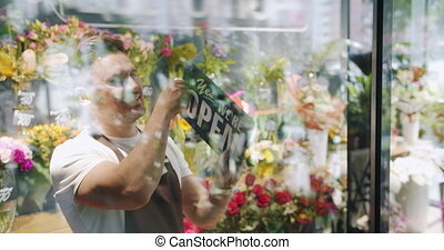 Handsome guy in apron changing open to close sign on flower...