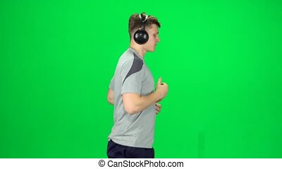 Handsome guy in big headphones is running, Chroma Key. Side view