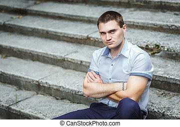 Handsome guy in blue shirt sitting