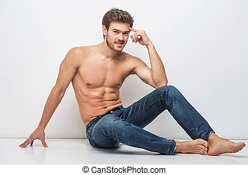 Handsome guy in jeans with bare torso. man sitting on floor near wall