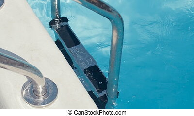 Handsome guy in swimming trunks up the aluminum ladder in the private swimming pool in slow motion