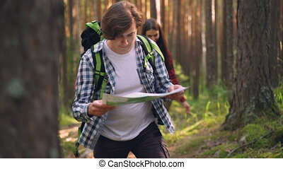 Handsome guy is holding map and walking in forest while his...