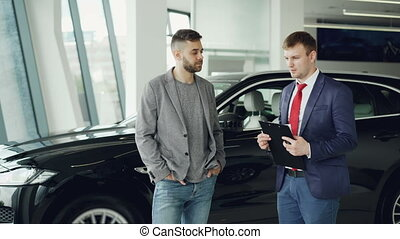 Handsome guy is talking to car dealership manager in motor...
