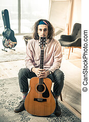 Long-haired peaceful man sitting on the chair with acoustic guitar