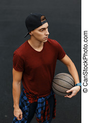 Handsome guy playing basketball, outdoors
