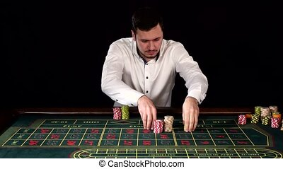 Handsome guy puts a bet in the casino. Black