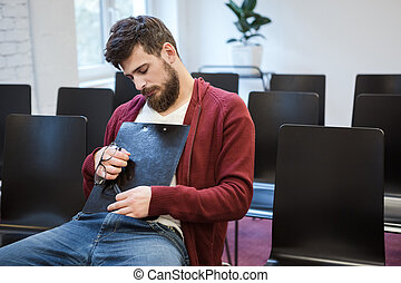 Handsome guy sitting and sleaping hugging clipboard