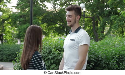 handsome guy smiling and talking with a girl holding her hand in the Park