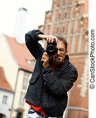 Handsome guy with a digital camera (shallow DoF)