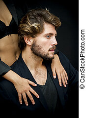 Handsome guy with a girl hands resting on his shoulder