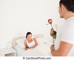 Handsome guy with a rose for his girlfriend in the bedroom