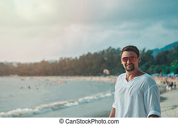 handsome guy with glasses on the beach background. Portrait of a man in white clothes