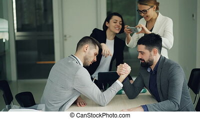 Handsome guys in suits are competing in arm wrestling...