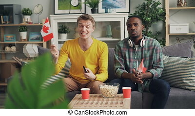 Handsome guys sports fans are watching competition on TV holding Canadian flags then celebrating victory having fun. Youth, friendship and house concept.