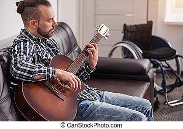 Handsome handicapped man enjoying his hobby
