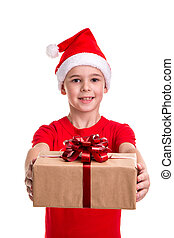 Handsome happy boy, santa hat on his head, holding out the gift box. Concept: christmas or Happy New Year holiday