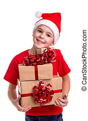 Handsome happy boy, santa hat on his head, with bunch of the gift boxes in the hands. Concept: christmas or Happy New Year holiday