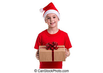Handsome happy boy, santa hat on his head, with the gift box in the hands. Concept: christmas or Happy New Year holiday