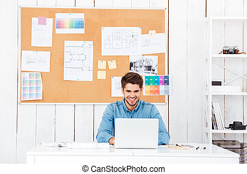 Handsome happy businessman working with laptop in office