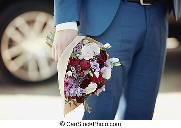 Handsome happy groom in blue suit with bouquet, car background