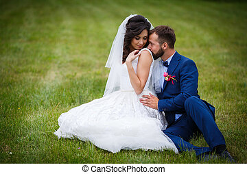 Handsome happy groom kissing beautiful bride on the shoulder while sitting in a field