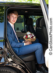Handsome happy groom sitting in car with bouquet