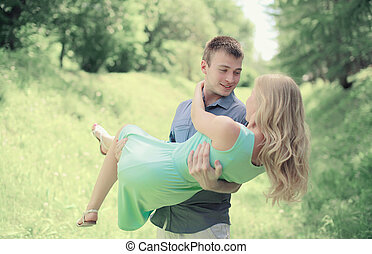 Handsome happy man holding on the hands favorite girl, couple, l