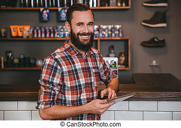 Handsome happy man with beard using tablet in barbershop