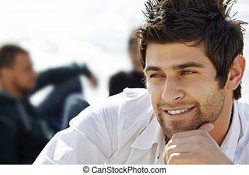 handsome happy turkish man with mullet haircut in white shirt with friends in the background