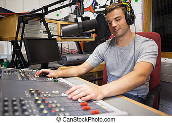 Handsome happy radio host moderating in studio at college