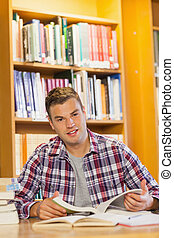 Handsome happy student studying his books in library