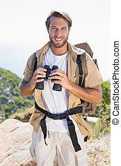 Handsome hiker holding binoculars on mountain trail