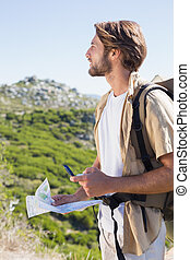 Handsome hiker holding map and compass at mountain summit