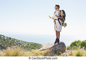 Handsome hiker holding map at mountain summit on a sunny day