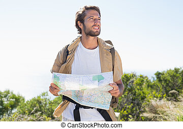 Handsome hiker holding map on mountain trail