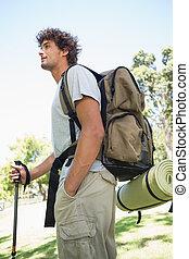 Handsome hiker holding walking pole