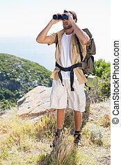 Handsome hiker looking through binoculars