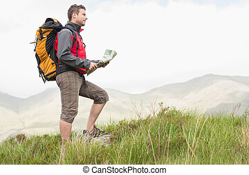 Handsome hiker with backpack hiking uphill holding a map in...