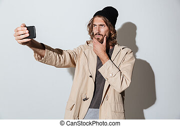 Handsome hipster man looking aside make selfie by phone