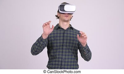 Handsome hipster man using virtual reality headset - Studio...
