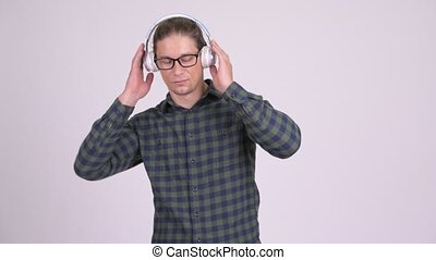 Handsome hipster man wearing headphones and listening to music